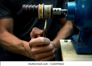 Working process of the leather walet in the leather workshop. Man holding demo walet and working with a machine. He's making edge of walet to be smooth. Tanner in old tannery.