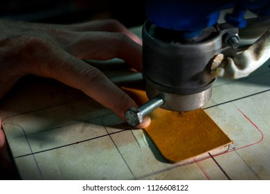 Working process of the leather walet in the leather workshop. Man holding leather craft and working with a machine. He's imprint logo. Tanner in old tannery.