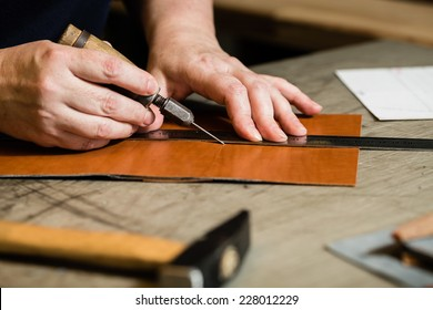 Working process of the leather wallet in the leather workshop. Woman's hands holding crafting tool and iron ruler.