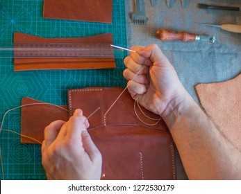 Working process in the leather workshop. Man holding crafting tool and working. He is sewing to make a walet. Tanner in old tannery