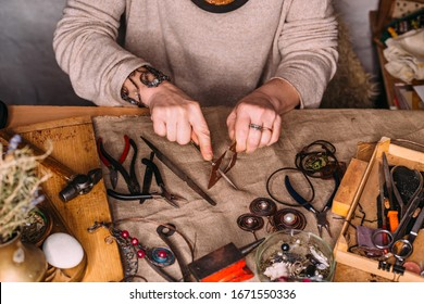working process making jewelry for wire wrapped bijouterie. real process. craft handmade copper wire working tools on the table with accessoires. handicraft people art concept
