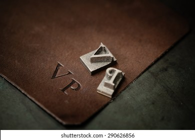 Working process of making leather wallet in the leather workshop. Vintage monogram emblem with letters V and P