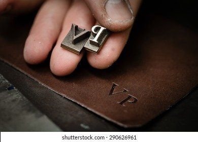 Working process of making leather wallet in the leather workshop. Vintage monogram emblem with letters V and P. Craftsman's hand holding the iron patters.