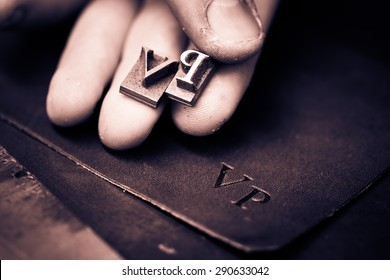 Working process of making leather wallet in the leather workshop. Vintage monogram emblem with letters V and P. Craftsman's hand holding the iron patters. Black and white photography. Cream toned.