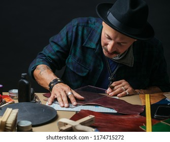 Working process of making shoes in workshop. Cobbler bewhiskered man holding crafting tool and working. Wooden table and dark background, close up. Footwear artisans and micro-entrepreneurs Concept