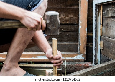 Working process. Men's hands at work. Clogging the boards. Tools - a big hammer - a sledgehammer. Against the black earth.