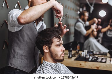 Working process in modern barbershop. Male hairdresser serving client, making haircut using metal scissors and comb, side view reflection in the mirrow.