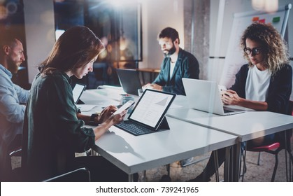 Working process photo.Group of young coworkers working together at night modern office loft.Teamwork concept.Blurred background.Horizontal