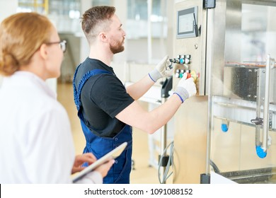 Working process at production department of dairy factory: bearded technician wearing overall adjusting equipment while his superior keeping eye on him