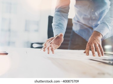 Working process startup. Businessman working at the wood table with new finance project. Modern notebook on table. Pencil holding hand. Horizontal mockup. Flares, film effect