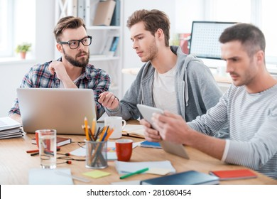 Working process. Three young business people working together while sitting at their working place in office