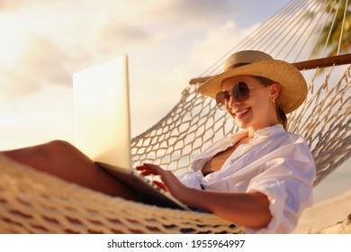 Fernbedienung. Seitliche Sicht auf junge glückliche Frau, freiberufliche Frau in Strohhut und Sonnenbrille, die auf Laptop arbeiten, während Sie in der Hängematte am Strand bei Sonnenuntergang entspannen. Fernarbeit während des Urlaubs