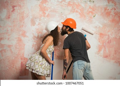 Working and repair. Builder man kiss girl in helmet with tool. Building and construction. Man and woman in hard hat. couple in love with repair roller on pink background.