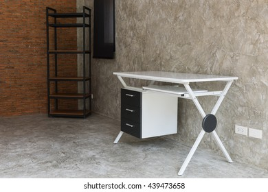 Working room with modern white table and wooden shelf over grunge red brick wall background