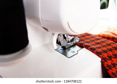 working in a sewing studio: sewing with a serger, overlocker. Fashion designers atelier