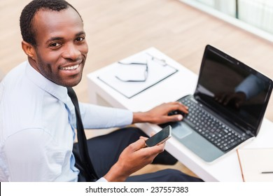 Working with smile. Top view of young African man in formalwear working on laptop and smiling while sitting at his working place