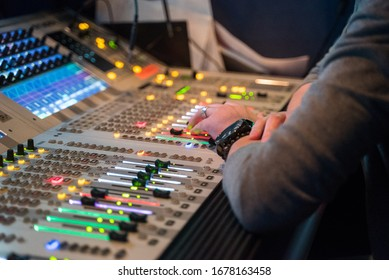 Working sound engineer hand on a audio mixer panel during broadcasting concert.