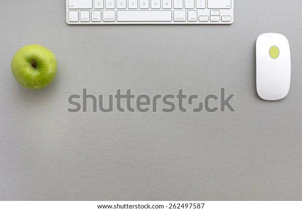 Arbeitsraum in grau-grün. Kreative Bürogestaltung mit grünem Apfel, Computertastatur und Maus auf grauem Holzschreibtisch. Draufsicht.