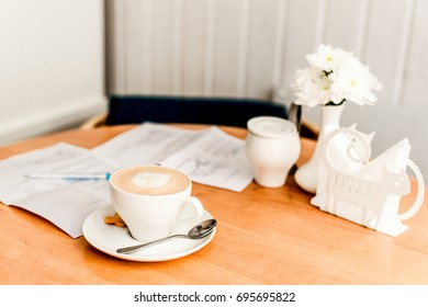 Working space. Paper, white cup with coffee on a wooden table. A modern concept of remote work, freelance, digital nomad.