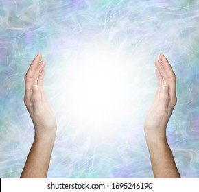 Working with spiritual healing energy - female hands 30cm apart opposite each other with a bright white light orb energy between against a pale blue energy field  background