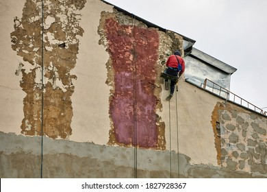 Working steeplejack with special equipment repairs the facade of the building. House walls cleaning and restoration works