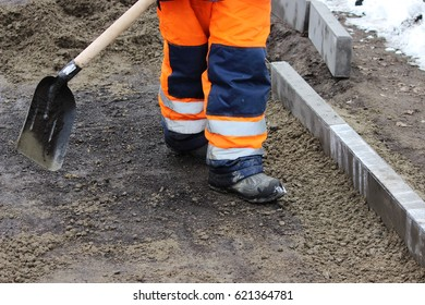 Working stonemasons repair the sidewalk, install curbs before asphalting for road