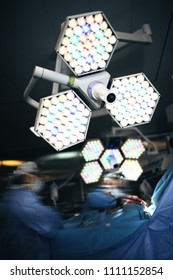 Working surgeons under the shadowless lamp in the surgery room.