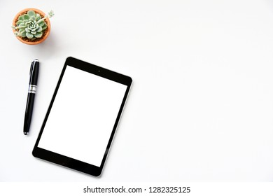 Working with tablet computer and Succulent copy space on table background.Top view style.Minmal workspace,business Concept