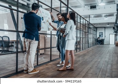 Working as a team. Full length of young modern people in smart casual wear planning business strategy while young woman pointing at large paper in the office hallway