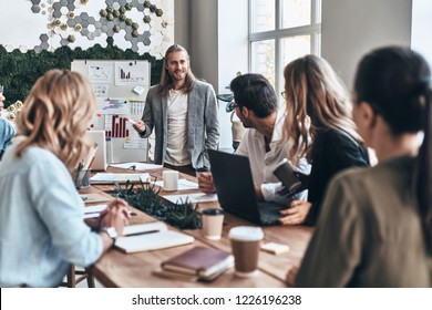 Working as team. Modern young man conducting a business presentation while standing in the board room