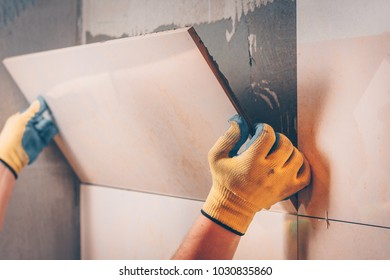 The working tiler removes the glued tile from the wall, the technology of professional and highly skilled tile work