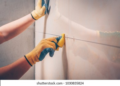 The working tiler wipes the tile on the wall with a damp sponge, removes the glue residues from the intertice seam, the technology of laying tiles and finishing