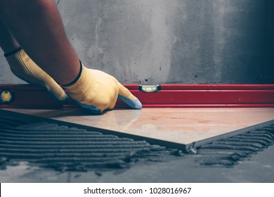 Working tiles lay a large tile on the floor