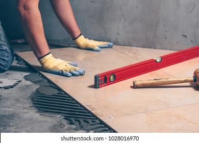 Working tiles lay a large tile on the floor, highly skilled work