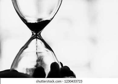 Working times countdown concept. Closeup Hourglass black and white vintage tone.