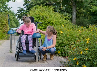 Working together with disability, a disabled girl in a wheelchair relaxing outside with her family