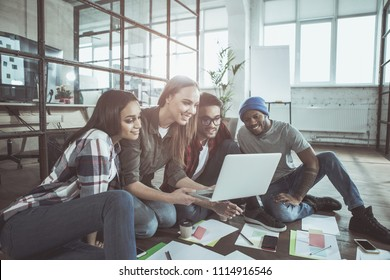 Working together is fun. Cheerful young colleagues are sitting on floor in cozy office and looking at screen of laptop in hands of attractive woman. They are expressing curious and togetherness