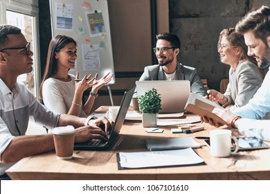 Working together. Group of young modern people in smart casual wear discussing business and smiling while sitting in the creative office