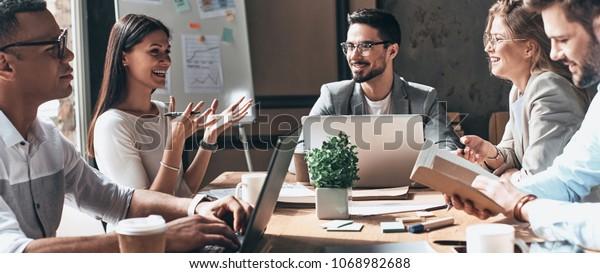Zusammenarbeit. Gruppe junger moderner Menschen in intelligentem Freizeitbekleidung, die im Kreativbüro Geschäfte diskutieren und lächeln