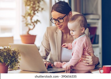 Working together. Young beautiful businesswoman using laptop while sitting with her baby girl at her working place