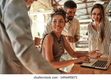 Working together. Young and cheerful afro american woman using laptop and discussing something with colleagues while sitting in the modern office. Teamwork. Office life