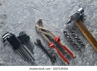 Working tool on a gray concrete background. Spanners, a hammer, hex keys. Top view, copy space.