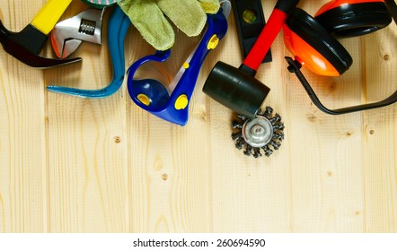 Working tools. Gloves, ear-phones, mount and other tool on a wooden background.