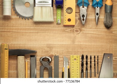 Working tools on a wooden boards background. Including saw, ruler, drill, nails, pliers,hammer, brush,thread,chisel and other.