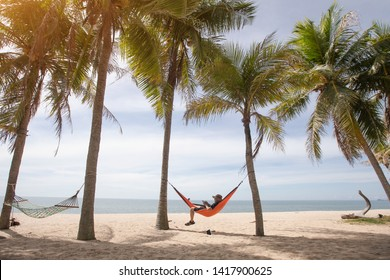Working in vacation concept. A man is lying in a hammock among the tall trees on the island.
