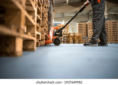 Working at warehouse. Low angle view of unrecognizable worker lifting palette with manual forklift.