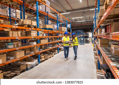 Working at warehouse. Two caucasian warehouse workers walking in distribution storage area discussing about logistics and organization.