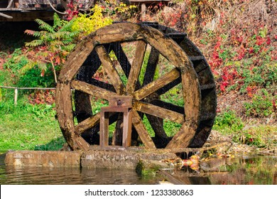 Working watermill wheel with falling water in the village.