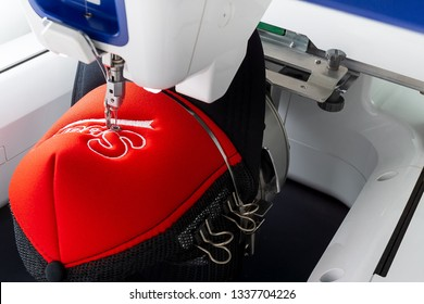 Working white embroidery machine embroidering logo on red and black sport cap, close up picture