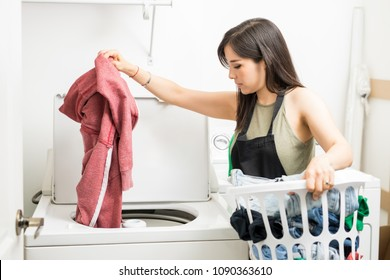 Working woman adding clothes to machine for a wash holding white laundry basket